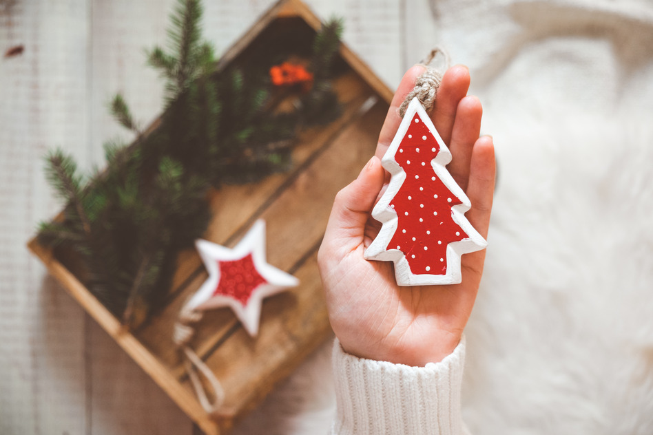 Wooden christmas toy in shape of spruce in womans hand